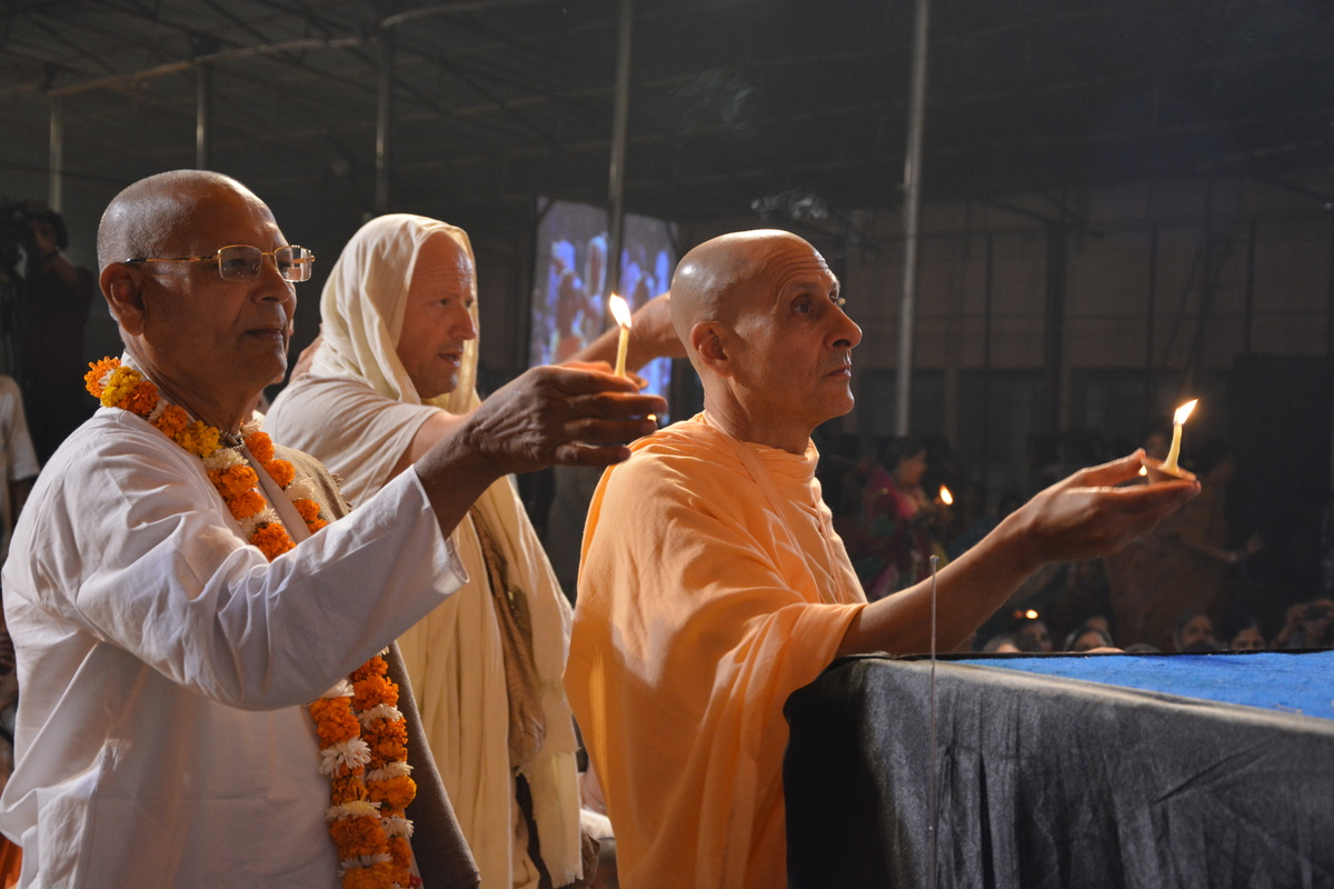 Radhanath Swami and Senior devotees offering lamps to Lord Damodar